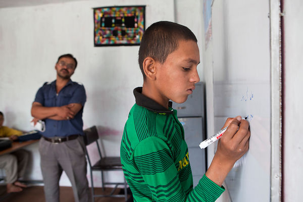 Bashir 13 ans écrit au tableau en classe, Kaboul, Afghanistan / Bashir 13 years-old is writting at the board in class, Kabul,...