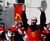 man marching in mediaeval costume holds trumpet above head in reenactment event Corsa all'Anello in Narni, Umbria, Italy