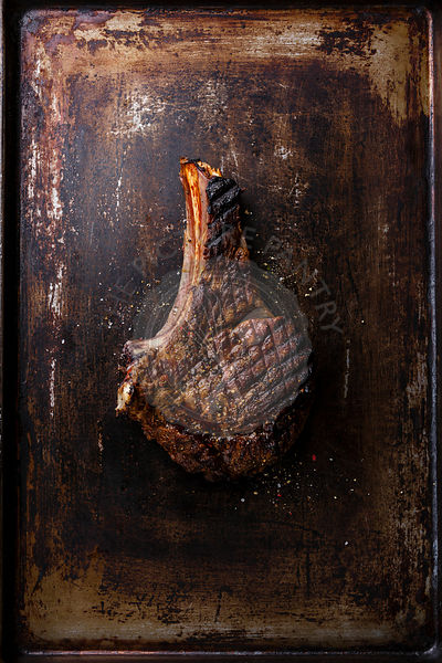 Grilled Ribeye Steak on bone on old scratched dark background