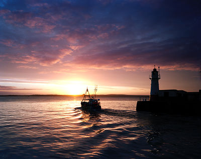 Spectacular sunrise over Mount's Bay with the trawler off to work once more passing the lighthouse at the end of Newlyn harbo...