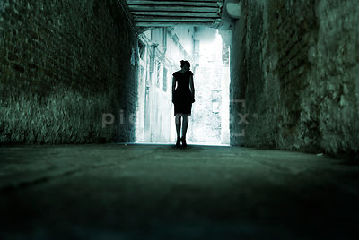 An atmospheric image of a mystery woman walking down in a narrow derelict street in Venice, Italy.
