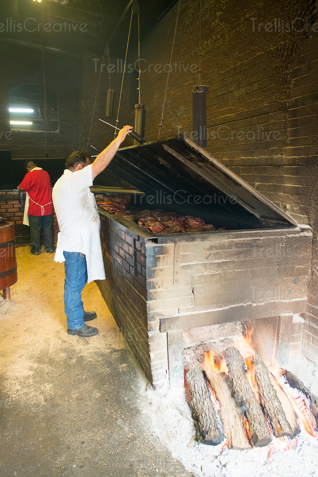 Chef looking at Barbecue grilled meat in restaurant