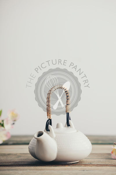 White teapot and sakura flowers on wooden table against the white wall