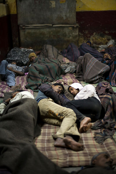 India - Delhi - Two young homeless friends lie together in the Fatepuri night shelter