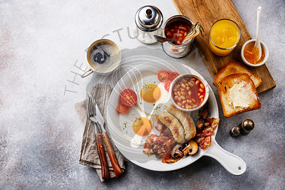 English breakfast in white pan with fried eggs, sausages, bacon, beans, toasts, orange fresh and coffee on white background c...