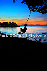 Children on a swing at sunset