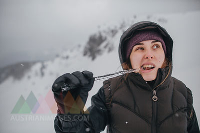 Austria, Kitzbuehel, portrait of young woman biting icicle