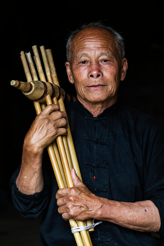 Portrait of a Black Hmong Man Holding a Traditional Musical Instrument