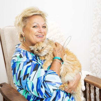 Senior Woman Holding Cat in Chair