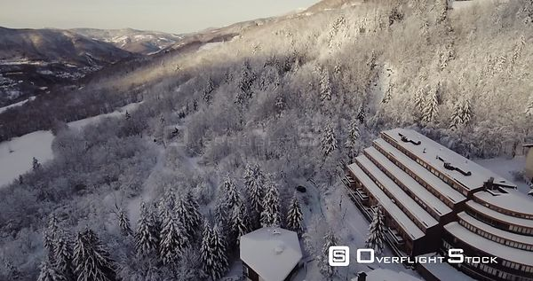Aerial, few houses in mountains under the snow in the middle of woods