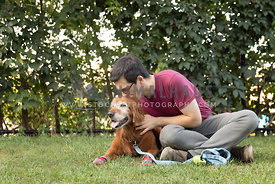 man kissing senior retriever dog