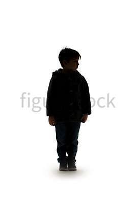 A Figurestock image of the silhouette of a boy standing - shot from mid level.
