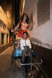 A boy transports an idol by bicycle during Kali Murti, Varanasi, India