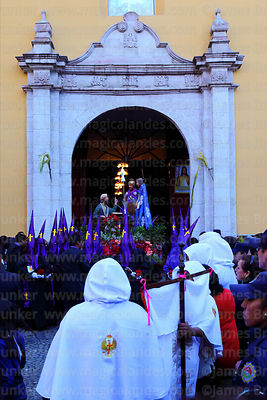 Penitents carrying statue of the Señor de la Sentencia / Lord of Judgment out of La Merced church at start of Good Friday pro...