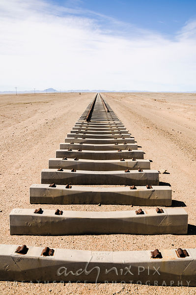 Rusted railway tracks ending, with empty concrete railway sleepers in the foreground, tracks disapearing into the desert in t...