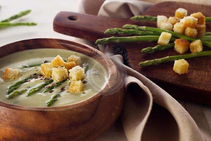 Asparagus soup cream with croutons on white background close-up