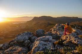 Woman sitting on rock on mountaint top, pointing at sunrise, view of Cape Flats, False Bay and Muizenberg Peak in background