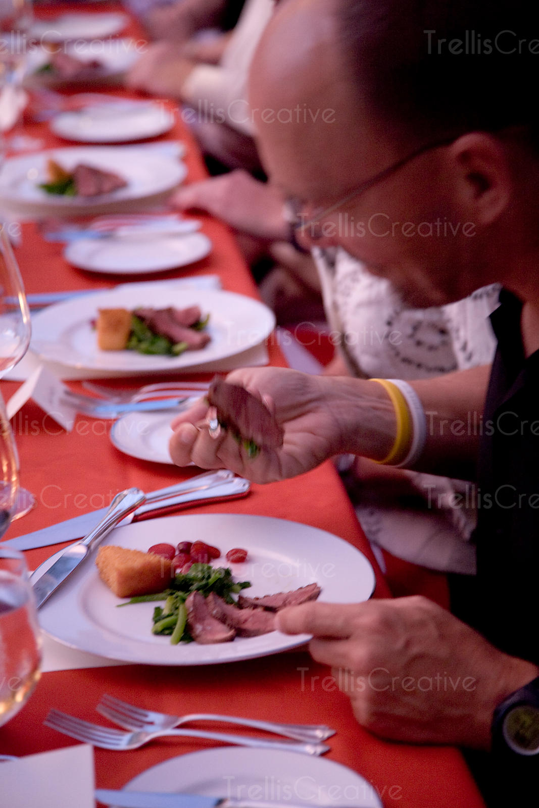 A guest in motion eating at a party