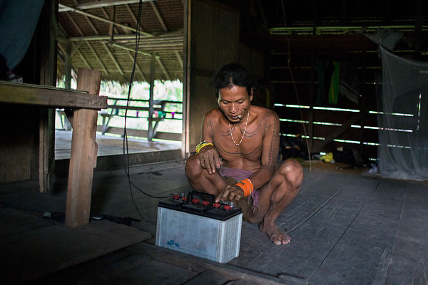 Amantari, 39, tries to connect a car battery to a light bulb before night, Pulau Siberut, Sumatra, Indonesia