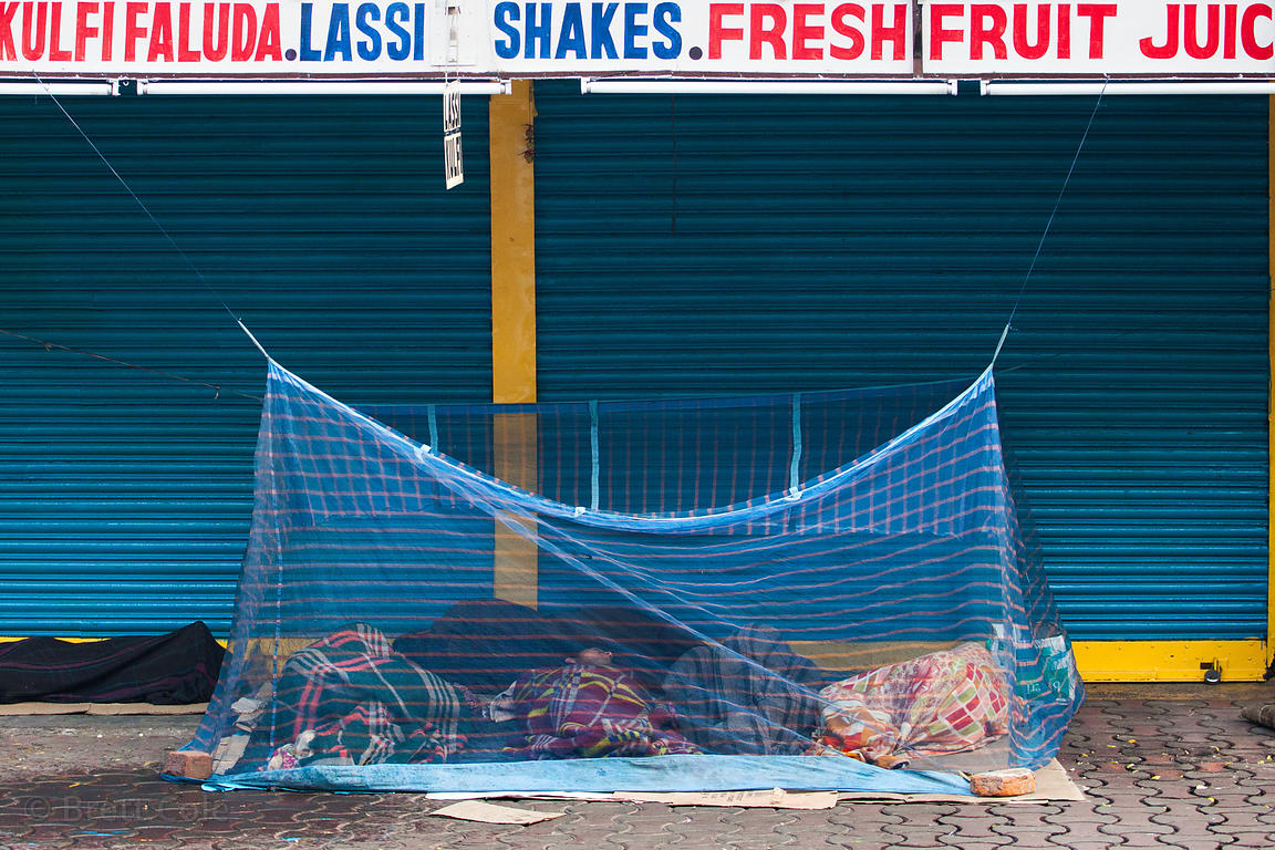 Homeless persons sleep inside mosquito netting on a sidewalk in Newmarket, Kolkata, India. The inexpensive mosquito nets can ...