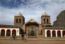 Men cycling past main entrance of colonial church, Ayo Ayo, La Paz Department, Bolivia