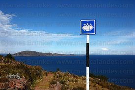 Community tourism trail sign and Taquile Island, Capachica Peninsula, Lake Titicaca, Peru
