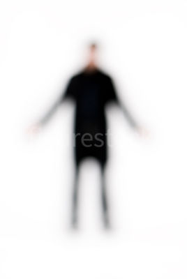 A blurred figure of a man standing with his arms out – shot from mid level.