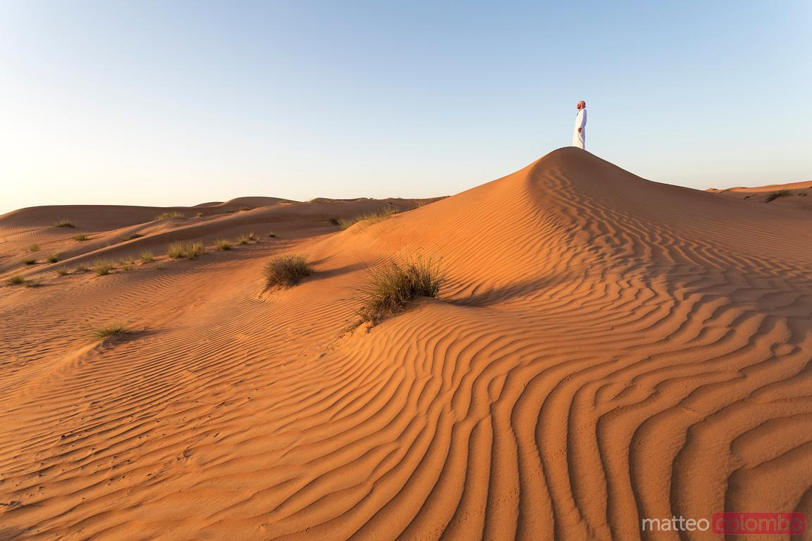 Oman, Wahiba Sands desert. Man with omani dress at sunrise