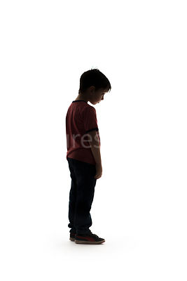 A silhouette of a boy standing in a t-shirt - shot from mid level.