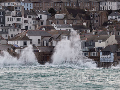 waves break on St Ives harbour sea wall