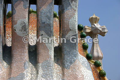 Roof of Gaudi-designed Casa Batllo in Barcelona, with ceramic spheres on ridge, glass & ceramic mosaic, chimneys, 4-armed cross