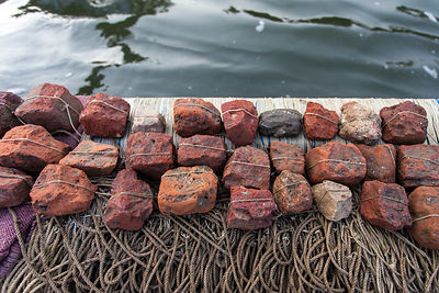 A series of fishing hooks tied to rocks, ready to be dropped in the Ganges River, Varanasi, India.