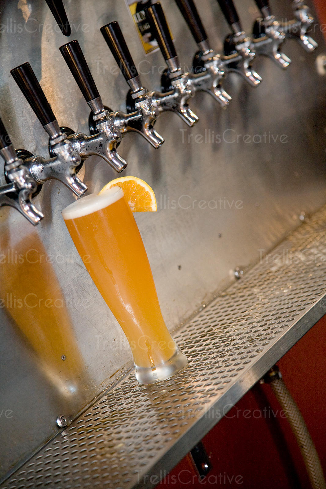 Freshly poured pint of wheat beer with orange garnish