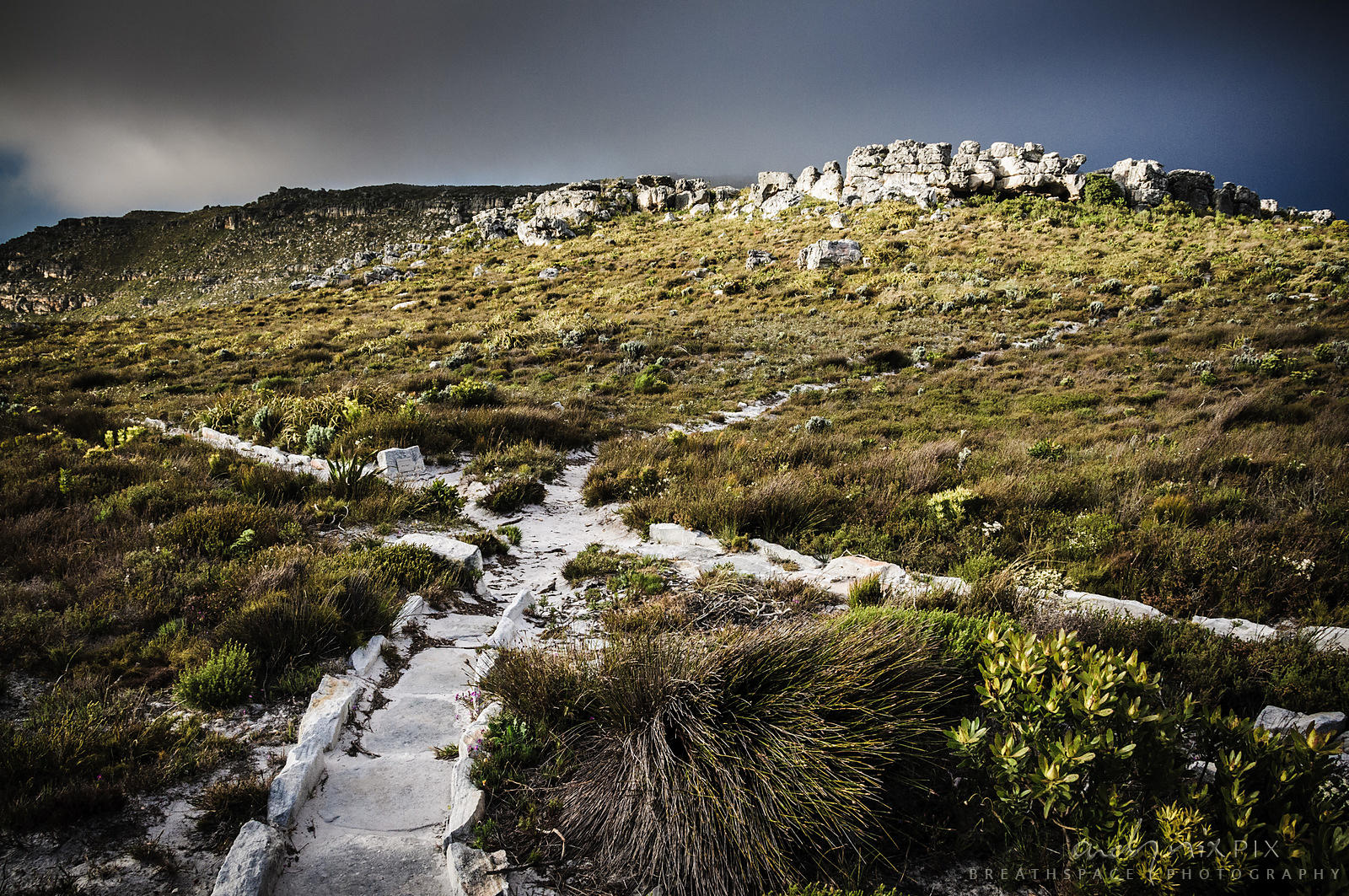 Cross roads of narrow hiking paths on mountain under dark and stormy sky
