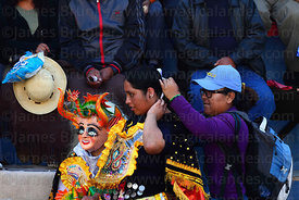 China Supay / female devil diablada dancer has her hair adjusted during the Gran Poder festival, La Paz, Bolivia