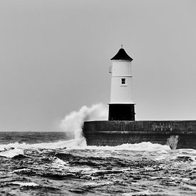 Waves breaking on a lighthouse against a clear sky in black and white
