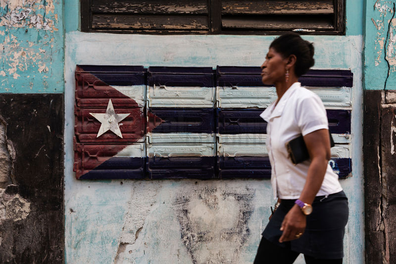Woman Walking in Front of Mailboxes in the Shape of a Cuban Flag