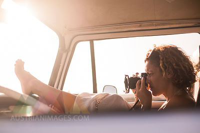 Woman sitting in parked van taking picture at sunset