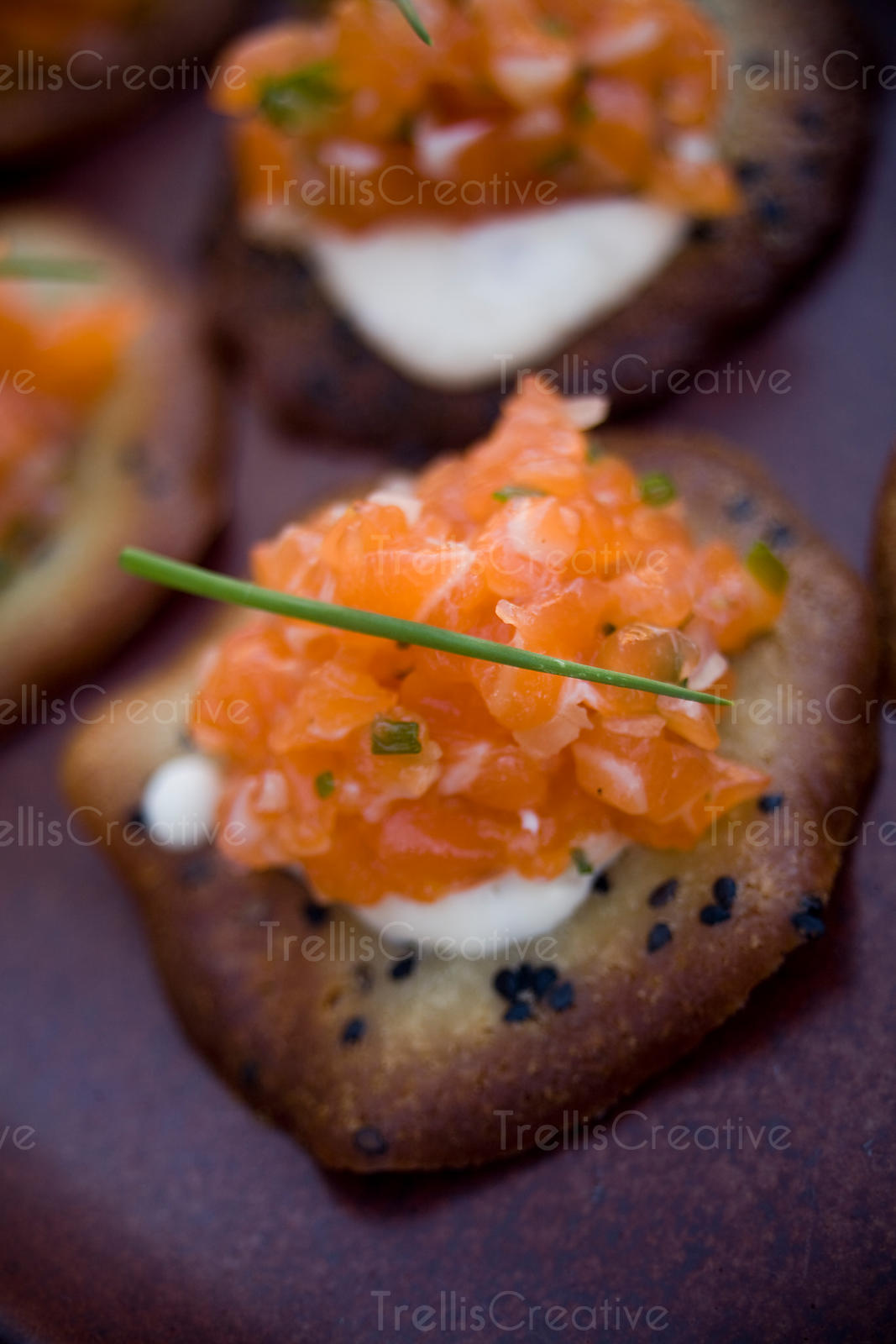 Salmon tartar on sesame crisps with creme fraiche served on stone platter