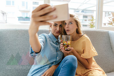 Two young women sitting on couch taking a selfie with sweets