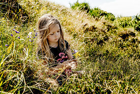 Little girl in the grass picking flowers 3