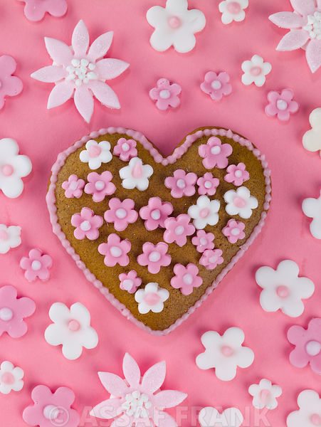 Heart shape biscuit with  flowers on pink background