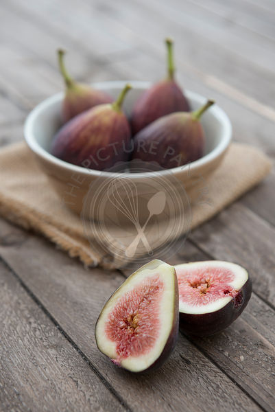 Figs in a bowl on a wooden background.