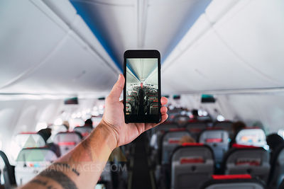 Airplane, man using smartphone, taking a picture interior