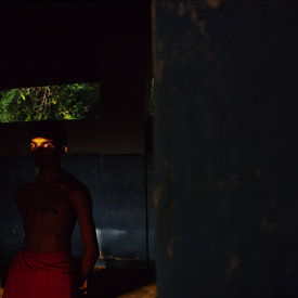 Arun, a student at the Kerala Kalamandalam, the State academy for kathakali, stands in a shaft of light after practice