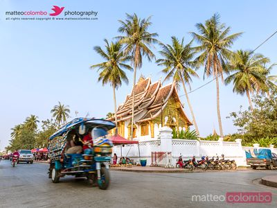 Street view with tuk tuk and temple, Luang Prabang, Laos