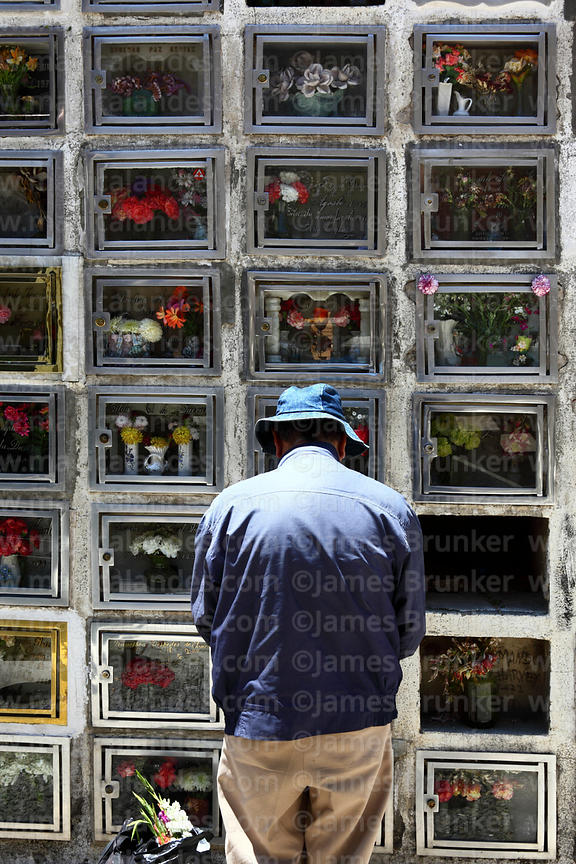 Man praying at tomb of relative in cemetery for Todos Santos festival, La Paz, Bolivia