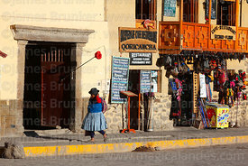 Quechua woman walking past craft shop and restaurant / cafe, Ollantaytambo, Sacred Valley, Peru