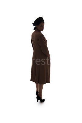 A silhouette of a 1940's woman in a coat, looking over her shoulder – shot from eye-level.