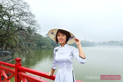 Young asian woman in traditional dress on famous bridge, Hanoi, Vietnam